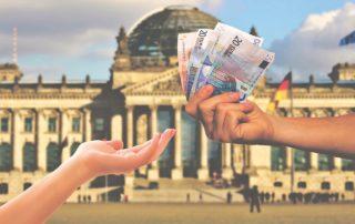 Deux mains s'échangent des billets (prêt de trésorerie) devant un bâtiment officiel