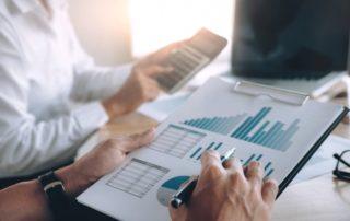 Un banquier et un client font le point sur des documents comptables à l'aide d'une calculatrice