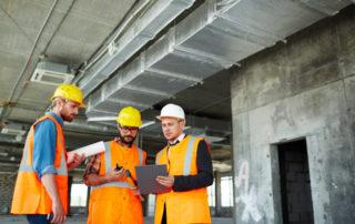 Trois architectes en gilet orange et portant des casques travaillent sur un chantier